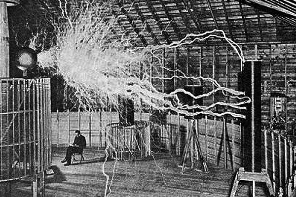Tesla sits below the Tesla Coil in his Colorado Spring Laboratory. The coil creates millions of volts of electricity with a frequency rate of 100,000 alterations per second.