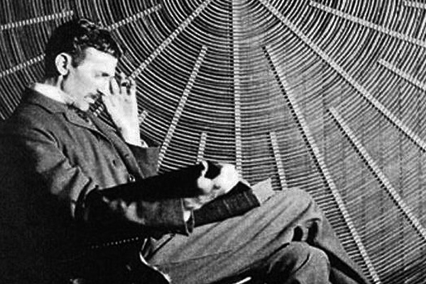 Nikola Tesla, with Roger Boskovich's book Theoria Philosophiae Naturalis, in front of the spiral coil of his high-frequency transformer at East Houston St., New York